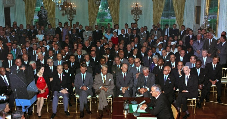 President Johnson enacting the Civil Rights Act of 1964 before a large audience.