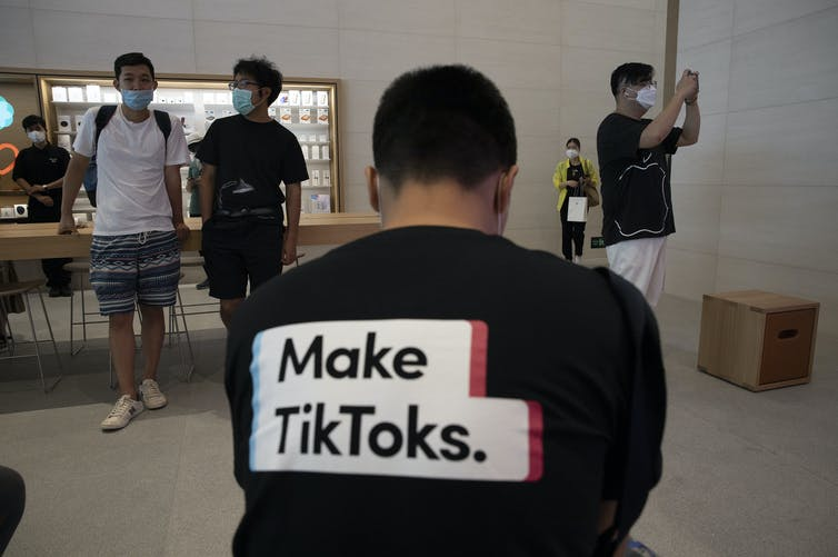 A photograph of a man's back wearing a shirt promoting TikTok in an Apple Store