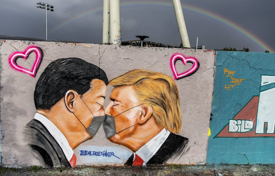 Grafitti artwork showing Xi Jinping and Donald Trump kissing with masks on.