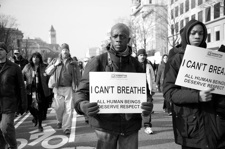 Two Black men carry posters with the words, 'I Can't Breathe'