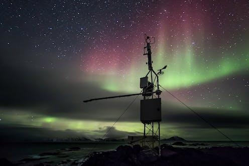 Estación meteorológica en el Ártico, con una aurora boreal de fondo.