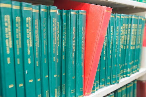 A row of green hardbound journals, with one with a red cover sticking out