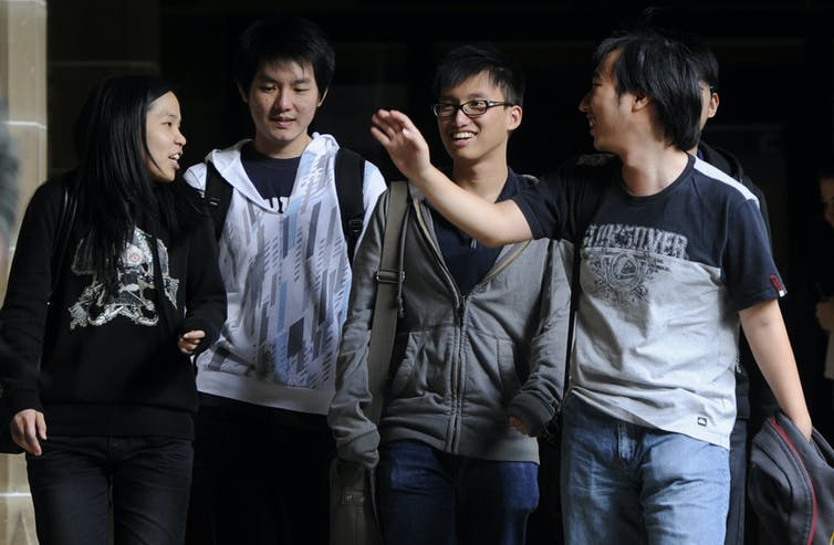 Group of university students smiling and chatting on campus