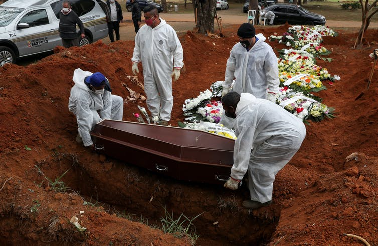 Gravediggers in protective suits lower a coffin into place alongside the graves of other coronavirus victims in Sao Paulo, Brazil