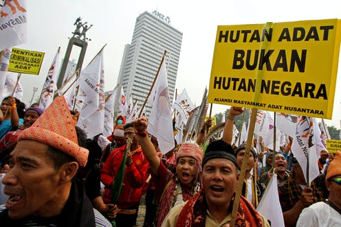 Dozens of men wearing traditional outfits holding protest signs.