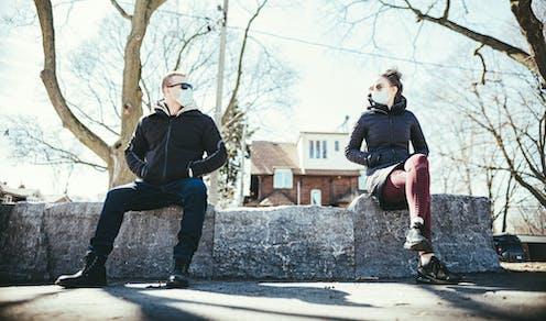 un hombre y una mujer sentados a cierta distancia en un murete y con mascarillas se miran.