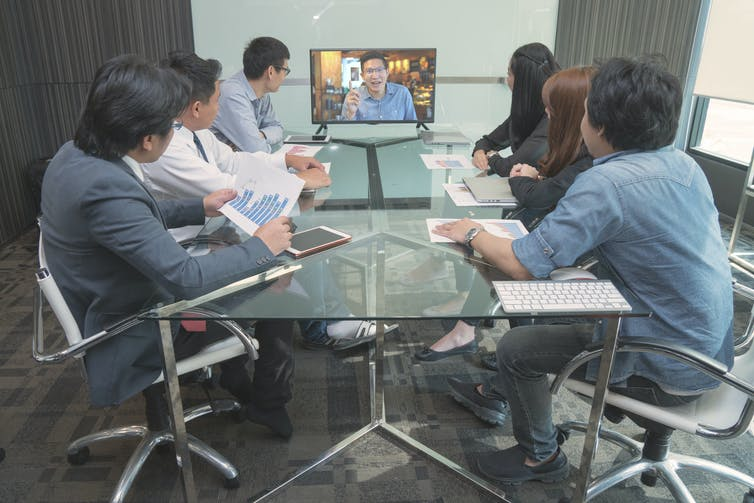A group of employees in a meeting in an office, with one employee present on a screen.