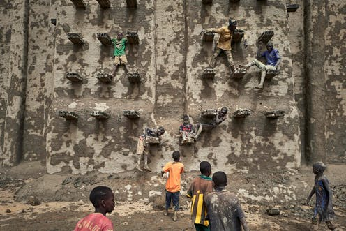 Children climb on the walls of a large mud brick structure as new mud is applied to it.