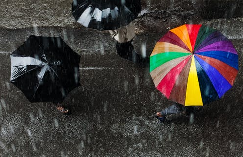 View from above of three people holding umbrellas in a heavy rain, one umbrella is rainbow colored and two are black.