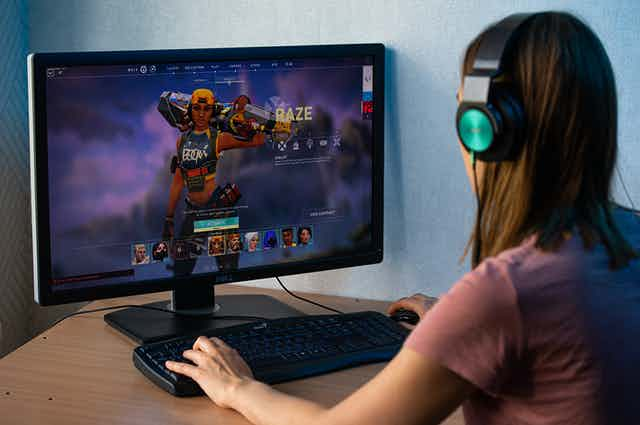 A young woman sits in front of a computer screen showing the video game Raze