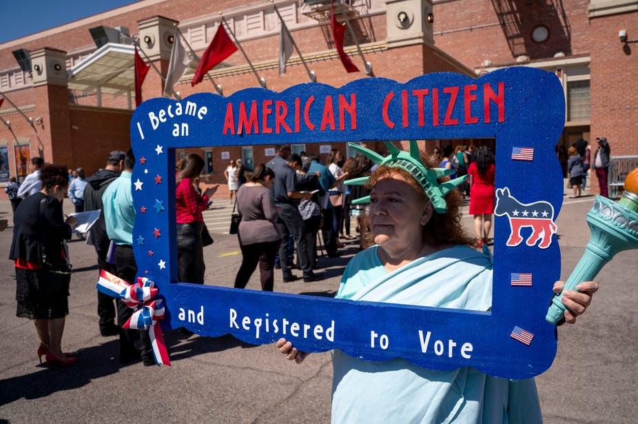A naturalized citizen dressed as Lady Liberty registering newly sworn in citizens to vote on April 18, 2019 in El Paso, Texas.