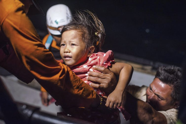 A girl is passed from a boat into the arms of a rescuer