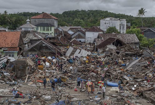 People mill around building debris