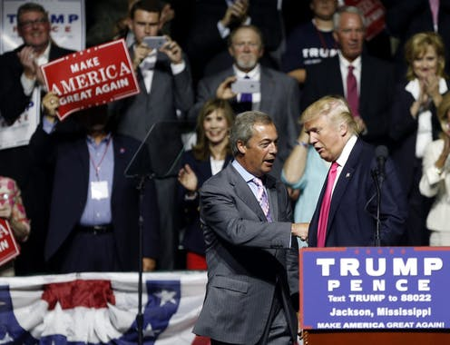 Farage and Trump shake hands in front of a Trump-Pence podium as someone waves a Make America Great Again sign.