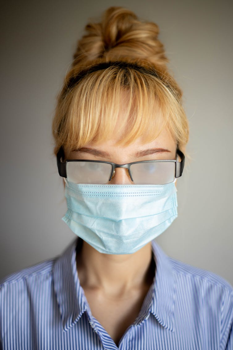 A woman wearing a face mask and eyeglasses with fogged-up lenses
