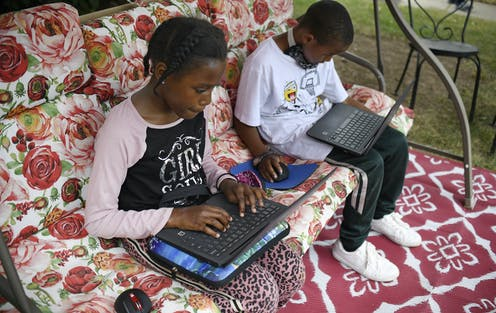 Fourth-grader Sammiayah Thompson, left, and her brother third-grader Nehemiah Thompson work outside in their yard on laptops provided by their school system for distant learning in Hartford, Connecticut.