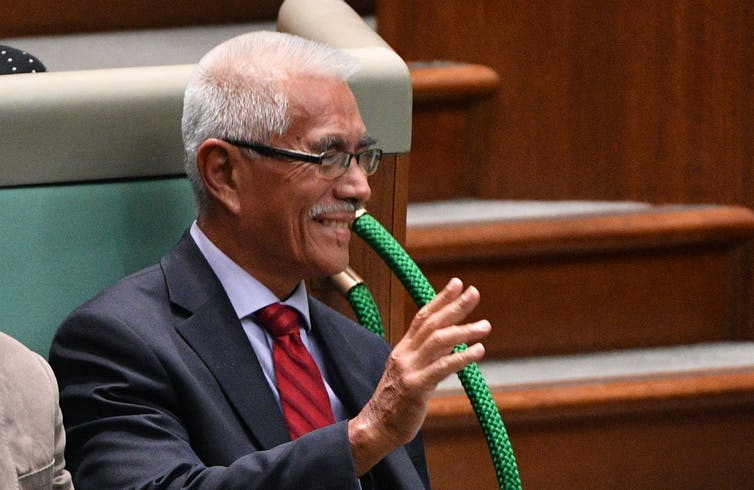 Former Kiribati president Anote Tong raises his hand while sitting in Australian parliament during question time.