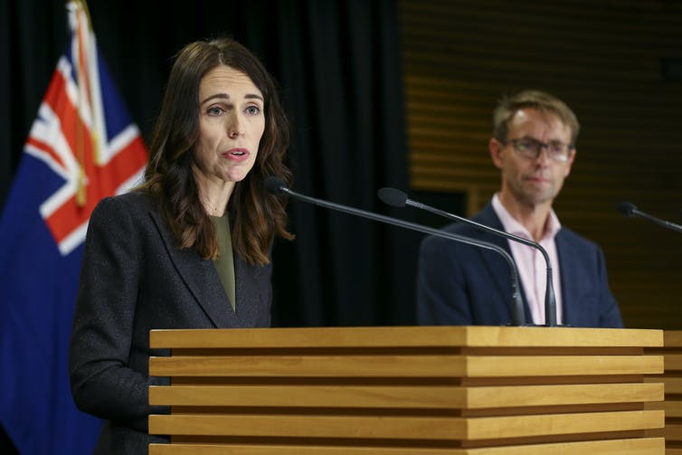 Jacinda Ardern at a lectern with NZ flag in background