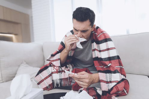 A man who is feeling sick and using tissues