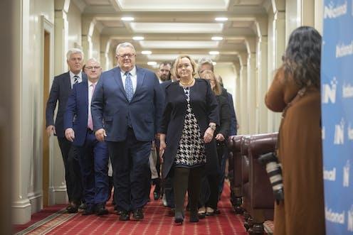 people walking down a corridor at parliament