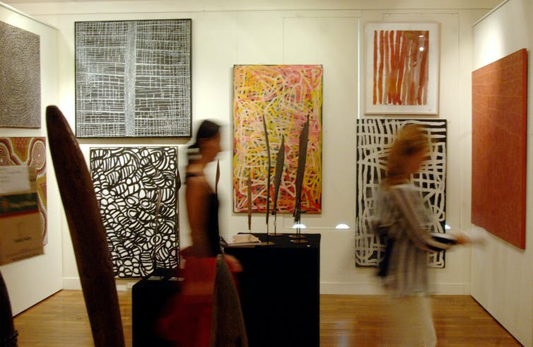 Gallery visitors look at Indigenous art works