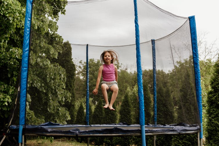 A young girl bouncing on a trampoline.