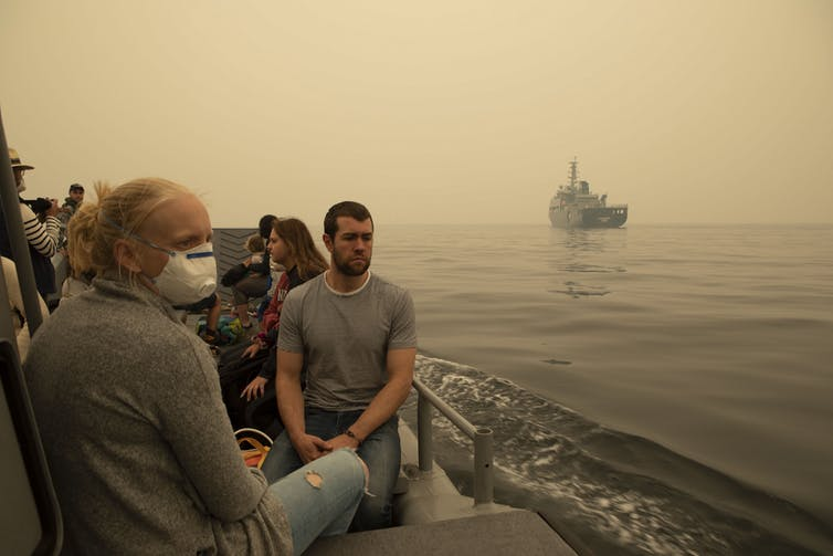 People on a boat wearing masks, surrounded by a haze.