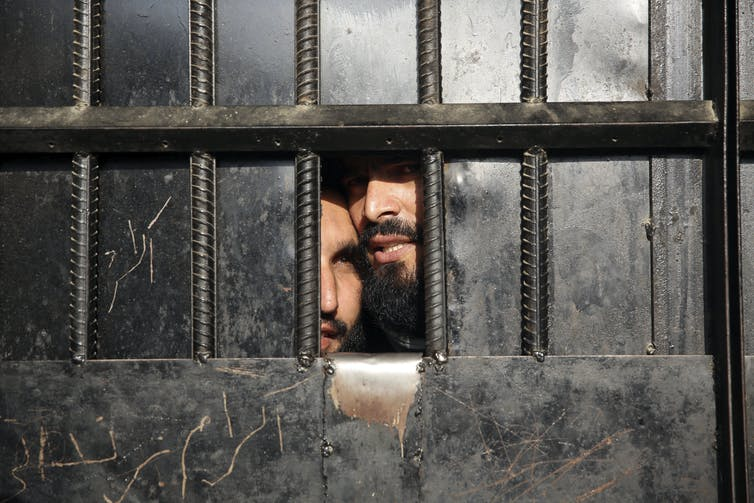 Taliban prisoners looking through a small window.