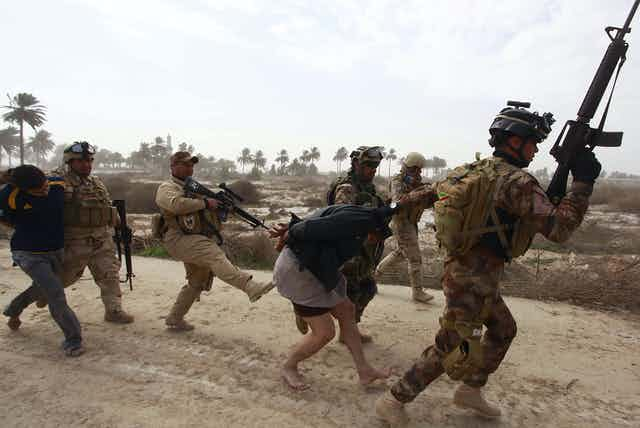 Iraqi security forces arresting suspected Islamic State militants