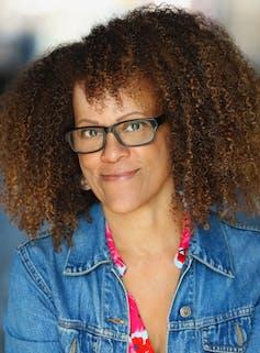 Novelist Bernardine Evaristo wearing a denim jacket and glasses