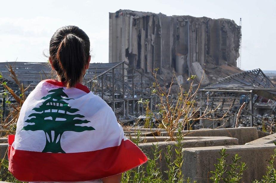 Une jeune femme fait face au silo de grain détruits sur le port de Beyrouth, le 11 août 2020.