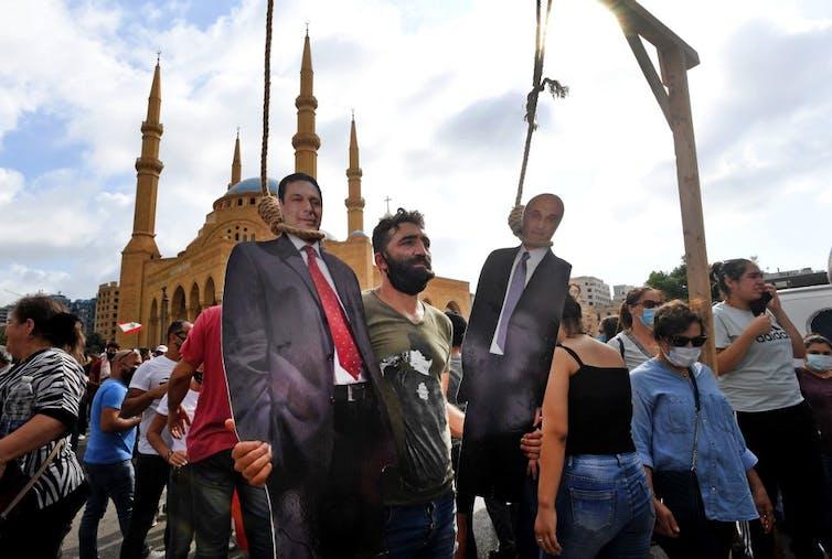 Des manifestants posent avec les effigies en carton du Premier ministre démissionnaire Hassan Diab et chef des forces armées Samir Geagea à Beyrouth