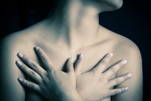 Una mujer se tapa los pechos con las manos.