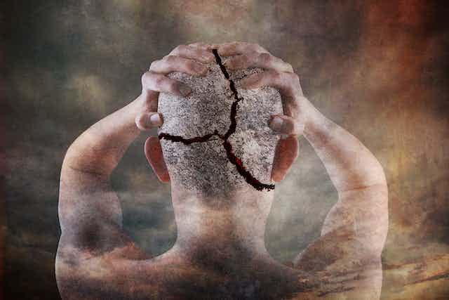 un hombre de espaldas se lleva las manos a la cabeza, que está agrietada.