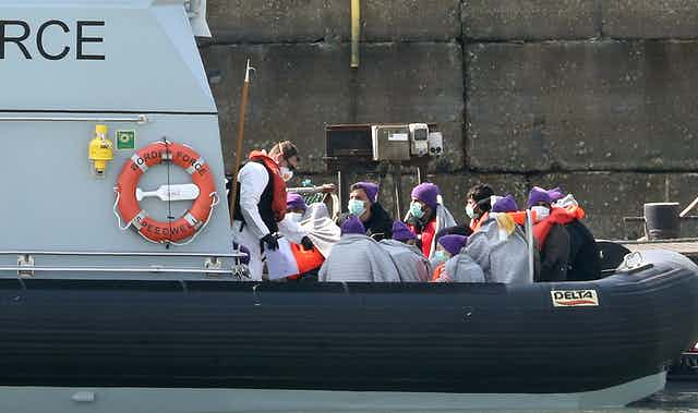 People arrive in the UK on a Border Force boat.