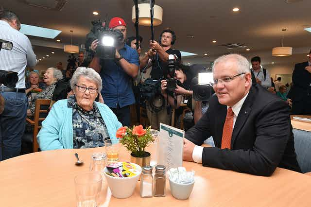 Scott Morrison sitting at a table with an elderly lady, at an aged care visit
