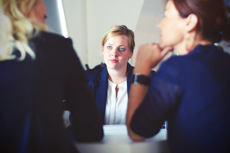 Three businesswomen sit in a board room in discussion.