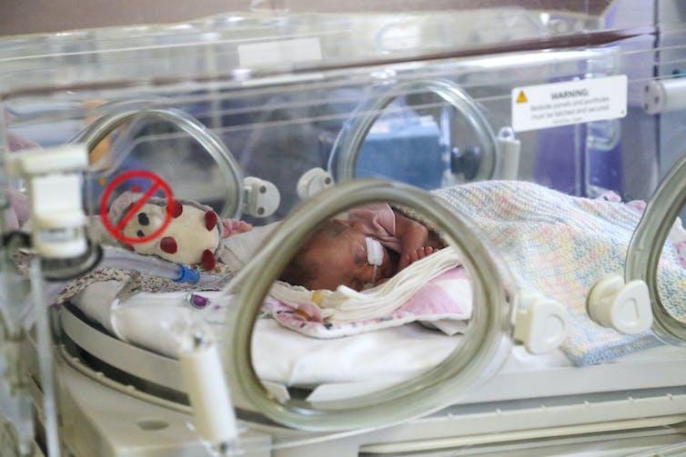 A baby sleeps in a crib at a maternity ward.