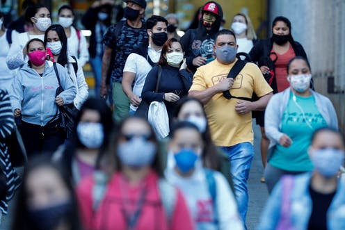 Busy street with people wearing face masks.