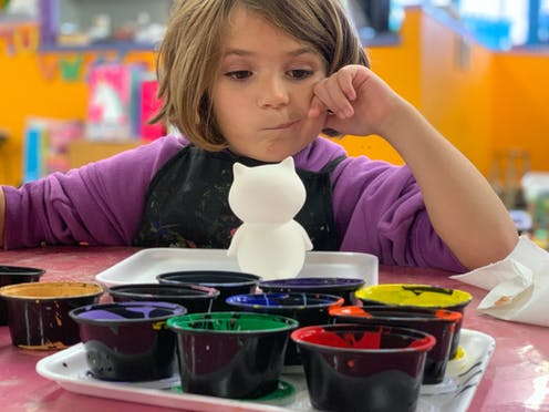 A young girl contemplates paint colours at a daycare centre.