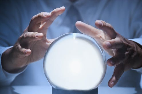 Hands around a glowing crystal ball.