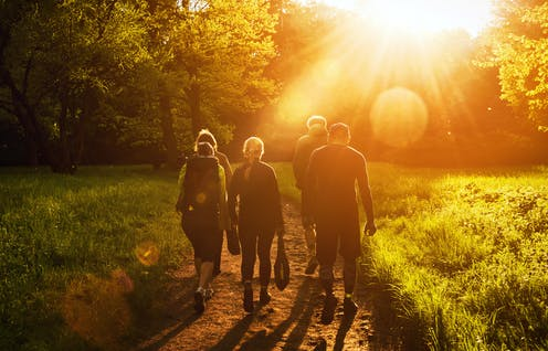 Group of young people walking towards sunset
