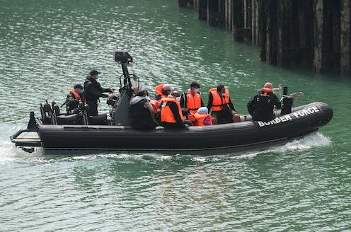 Men arrive in the UK on a border force boat.