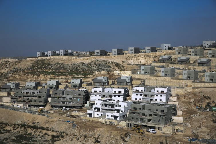 Houses under construction on an arid hilltop in the West Bank