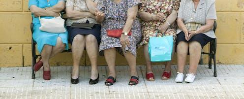 Cuatro señoras mayores sentadas en un banco.