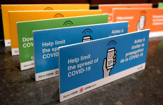 """a photograph of blue, green and yellow placards placed in a row with the text: """"Help limit the spread of COVID-19"""""""