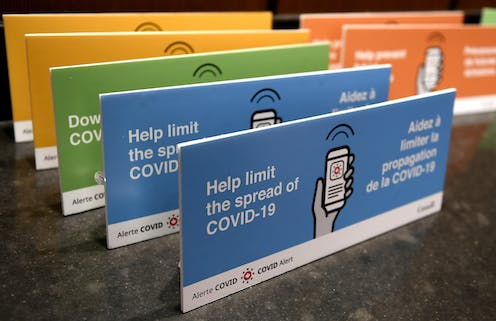 "a photograph of blue, green and yellow placards placed in a row with the text: ""Help limit the spread of COVID-19"""
