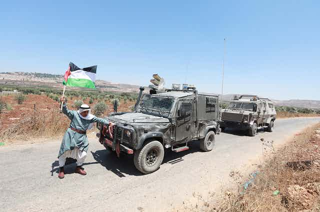 Elderly man with Palestinian flag confronts Israeli soldiers in armored vehicles
