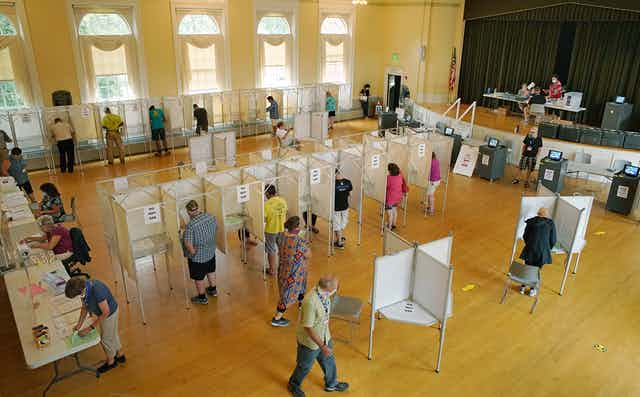 A polling place in a public building with booths and voters.