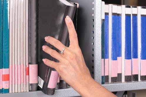 Hand removing a book from a shelf of journals and books